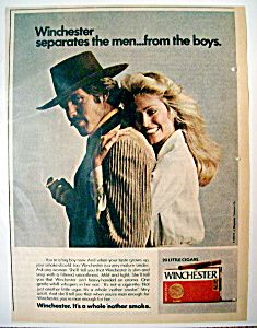 """This vintage Cigar magazine ad depicts """"Farrah Fawcett"""" hugging a man holding a """"Winchester Cigar"""". (1974)"""