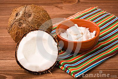 The pulp of coconut in the bowl. Coconuts are whole and chopped. Wooden table