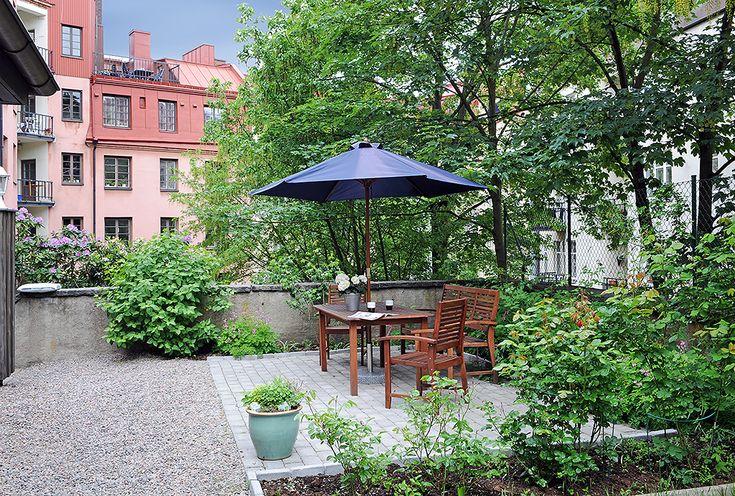 Grönskande innergård med sittplatser grill