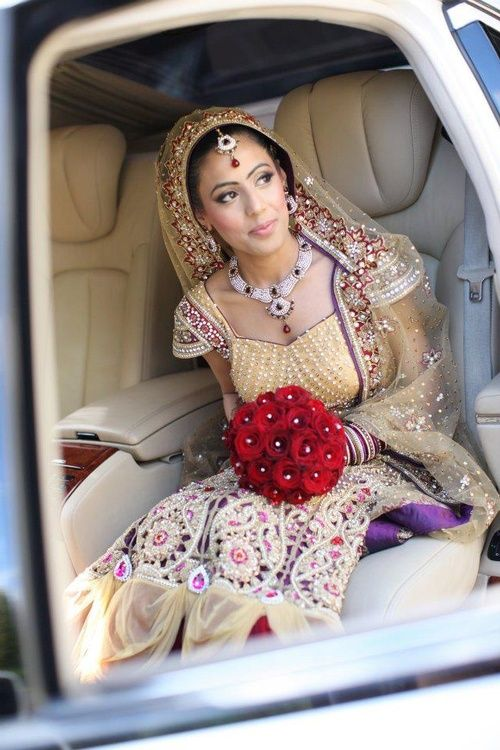 Beautiful Indian bride in beige and purple with bright red wedding bouquet flowers.