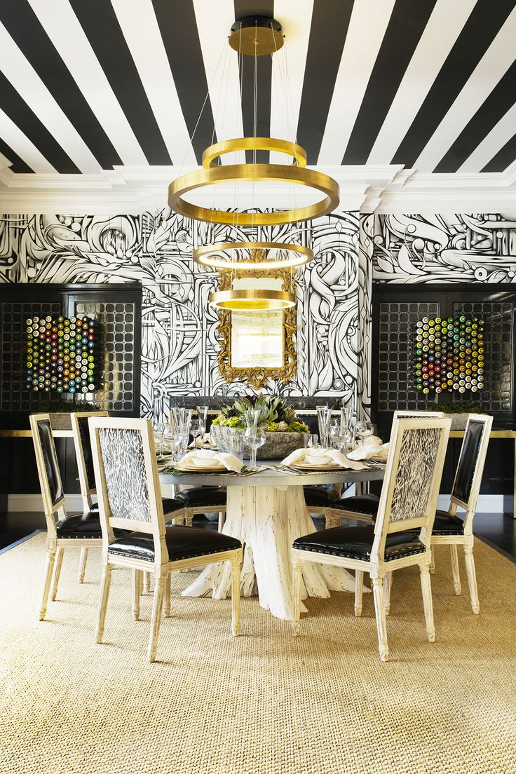 Striped ceiling, graphic wallpaper and modern light fixture above traditional dining table and chairs in glamorous dining room
