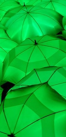 Umbrellas, lighted from beneath, perhaps by neon green strips.