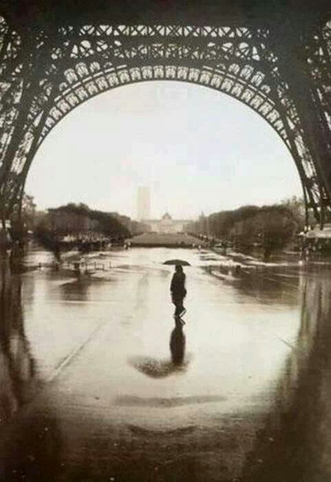 This picture of someone with an umbrella in the rain under the eiffel tower reminds me of the time I got stuck in the rain in Barcelona.