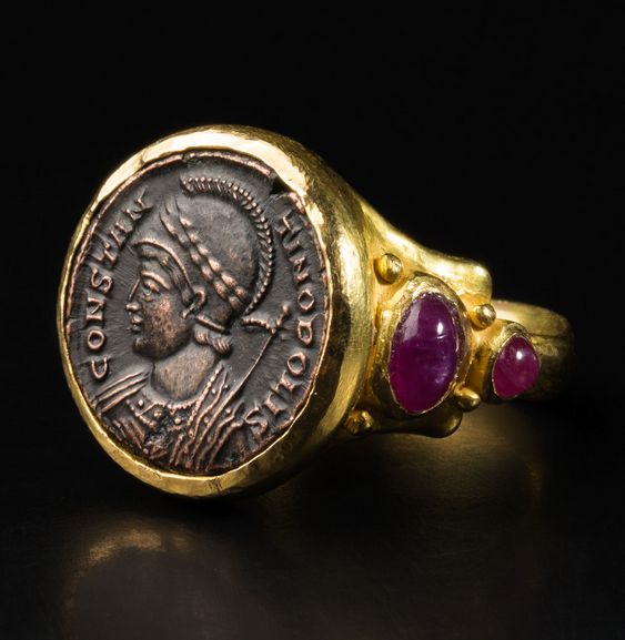 Gold Ring with Ancient Roman Coin of Emperor Constantine (306 - 346). 18-karat gold ring, created by the vendor in Italy, decorated with four cabochon rubies and set with a bronze Roman coin commemorating the New Rome: Constantinople. The coin is of a type minted under Constantine I and his sons, and put in circulation between 330 and 346