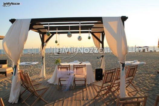 Perchè non sposarsi in riva al mare? Pedana, sedie e gazebo in legno, allestimento semplice per un matrimonio a suon di musica e onde