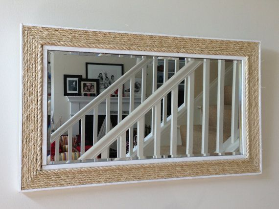 I can totally make this .. frame out the current mirror and then hot glue the rope .. cheap at lowes..