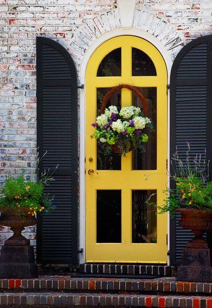 Yellow door, black shutters, basket and urns of flowers