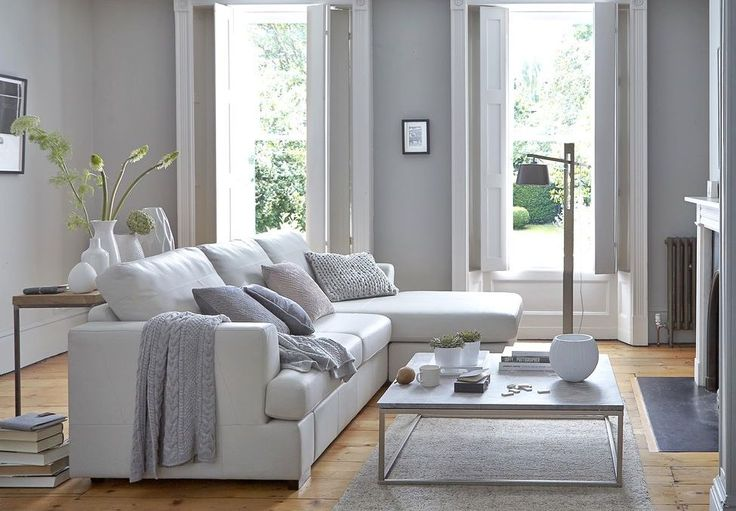 A corner sofa, such as this leather Freya from DFS, can help to give shape to a featureless room. A console table arranged with tall vases is a clever idea that gives the scheme height.