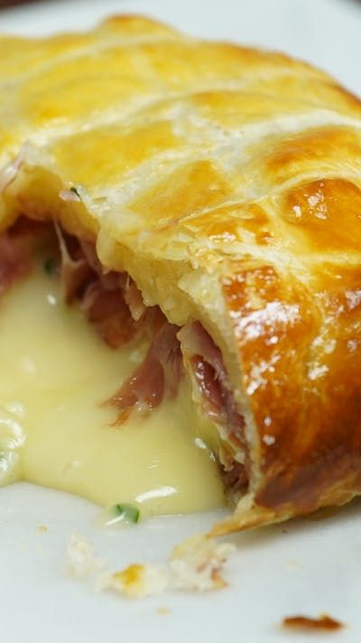 Recipe with video instructions: Ham wrapped, whole camembert in a delicious pastry parcel. What's not to love? Ingredients: 1 whole camembert, 6-8 slices of prosciutto , 5 garlic cloves , Small bunch of chives, 1 pack of puff pastry, 1 egg yolk, beaten, Flour for dusting
