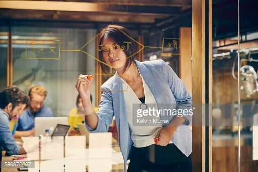 Stock Photo : An Asian professional writes on window in meeting