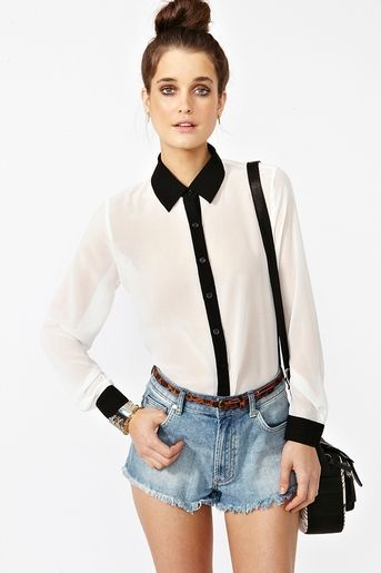 Chic ivory chiffon blouse featuring a black collar, cuff and button-down front. Cut longer at back, flowy fit. Looks fab tucked into leather skinnies with towering platforms!