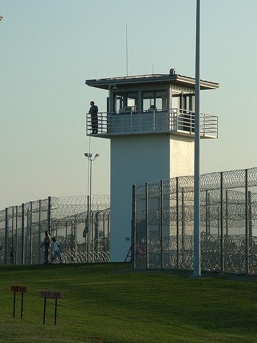 Prison GuardI wanted to get a picture of a prison tower with a guard in it. We lucked out at driving up when a guard was delivering something to the tower guard. He is just now lifting the bag up. This was at the Holiday Unit
