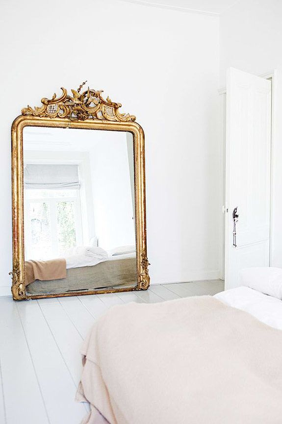 Gorgeous oversized gold mirror in simple room with white walls and white floors