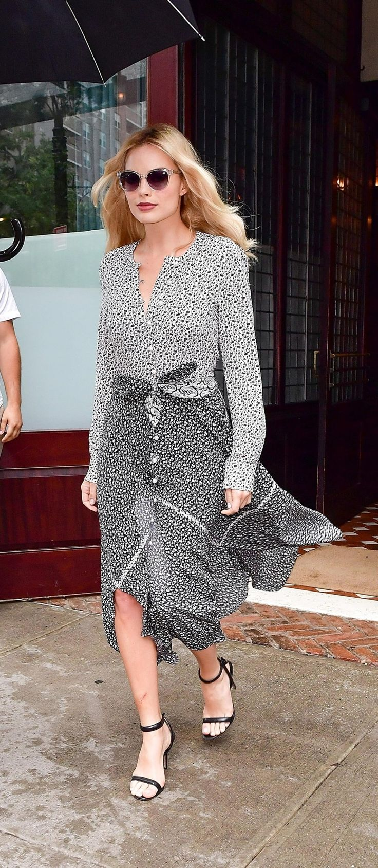 Margot Robbie in a black-and-white mixed floral Altuzarra dress with pearl buttons and a handkerchief hem.