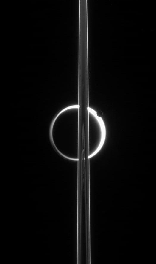 kenobi-wan-obi: Candle in the Dark Saturn's rings cut across Titan's luminous crescent  globe-encircling haze, broken by the small moon Enceladus, whose icy jets are dimly visible at its south pole. The scattered light around planet-sized Titan (5,150 km, or 3,200 miles across) makes the moon's solid surface visible in silhouette. Enceladus (505 km, or 314 miles across) enjoys far clearer skies than its giant sibling moon. This view shows the unlit side of Saturn's rings.