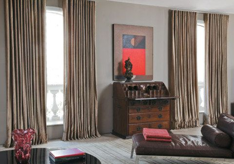 """Com piso de mármore, a sala desta casa pedia materiais e revestimentos que deixassem o ambiente mais aconchegante. """"Na hora de escolher o tecido das cortinas, pensei logo no veludo"""", afirma a proprietária, Helena Tourinho, que contratou o arquiteto baiano David Bastos para cuidar da decoração. A cor fendi da parede definiu o tom das peças, que pendem majestosamente no ambiente, formando pregas onduladas em um varão com sistema de trilho. """"Elas acabam funcionando mais como xales, pois gosto…"""