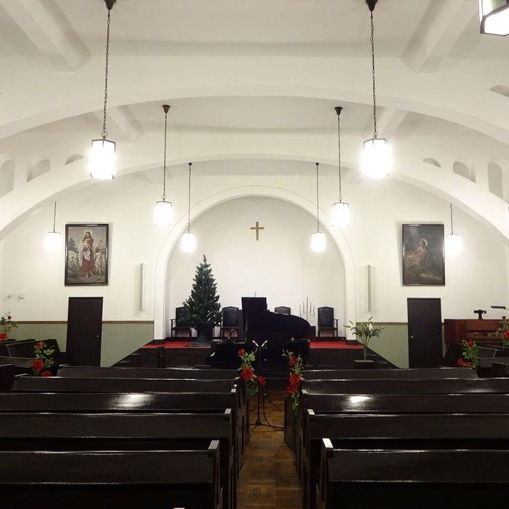 礼拝堂にて開催されたフルートリサイタルの開演前風景アドベント期間中ということもありキリスト教のシンボルと演奏テーマをとりまぜた演出での舞台脇装花 赤い薔薇白い百合マドンナリリーアドベント花 舞台装花