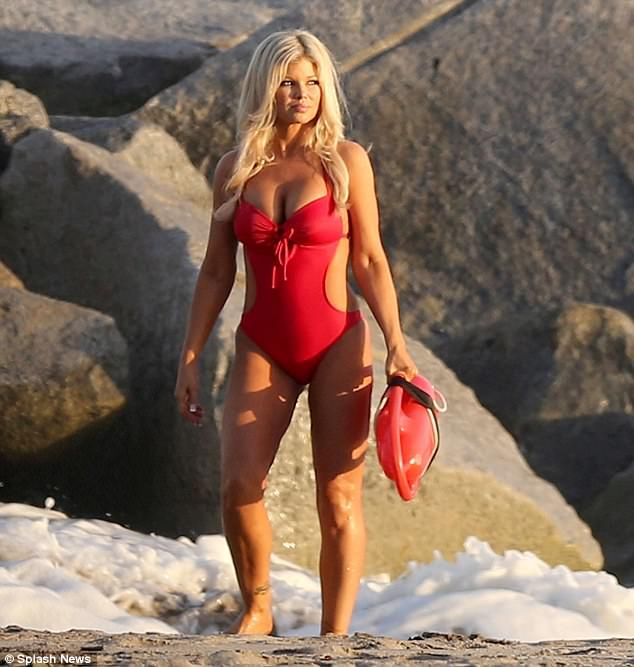 She's still got it! Donna D'Errico looked stunning in a red Baywatch style swimsuit as she held on to a float on a Malibu beach on Wednesday