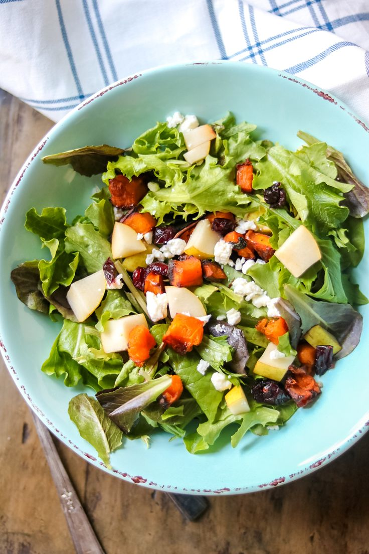 Roasted Butternut Squash Salad with Pears, Feta and Apple Cider Viniagrette: Butternut squash stars in this easy Fall Salad with Mixed Greens Salad in a Blue Pottery Bowl on a wooden table with a white and blue towel in the background