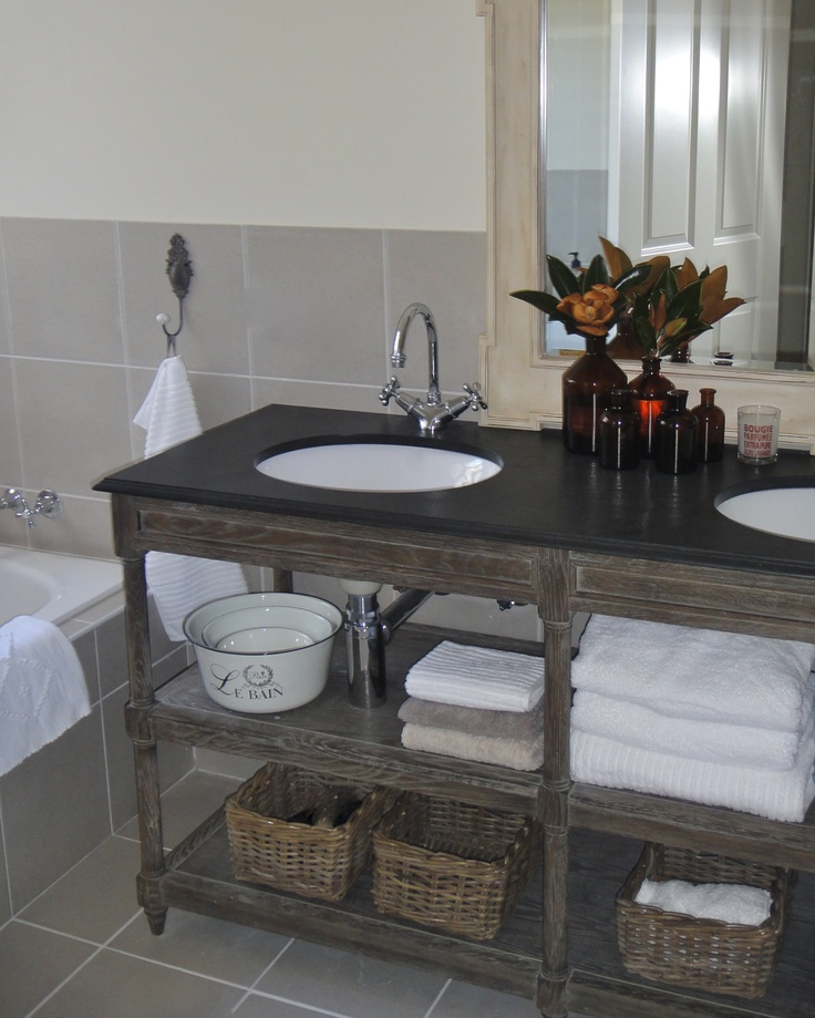 French Provincial style bathroom vanity in greyed oak with black limestone top.