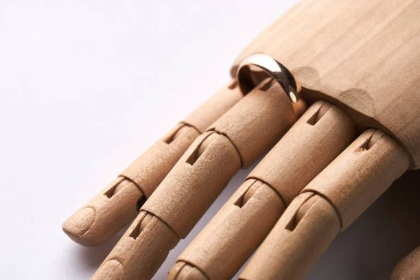 prosthetic wooden hand with wedding ring on ringfinger