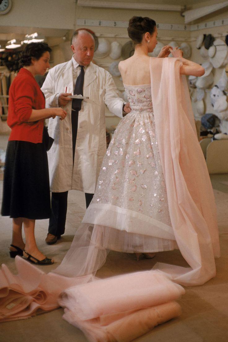 Christian Dior ajustando un vestido a una modelo en Paris. Febrero 1957