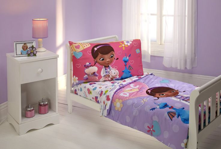 doc mcstuffins toddler bedding set. 4 piece set with a purple comforter, flap top and fitted sheet, and a pink pillowcase.