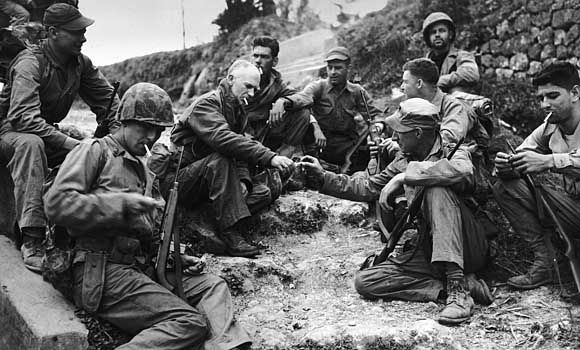 """""""You feel small in the presence of dead men, and ashamed at being alive, and you don't ask silly questions."""" War journalist, Ernie Pyle (center-left). Photo via War History Online."""