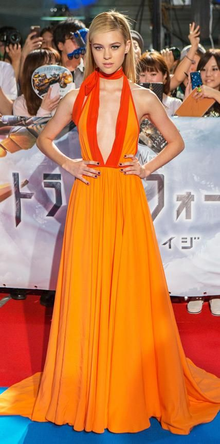 Look of the Day › July 29, 2014 Nicola Peltz sizzled at the Tokyo premiere of Transformers: Age of Extinction in a sweeping orange Prada creation with a downtothere neckline and necktie.