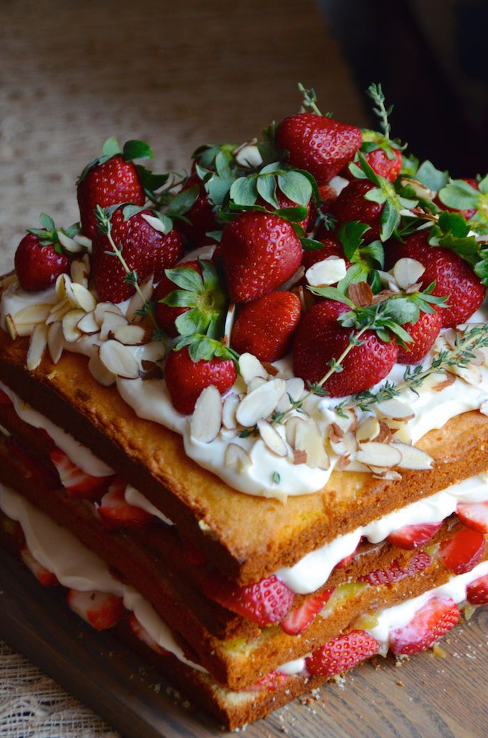 Get the recipe for this big gorgeous naked cake made from almond cake layered with fresh strawberries, honey and rosewater cream cheese frosting, lime curd, and sliced almonds. A big gorgeous showstopper of a cake that requires zero decorating skills.