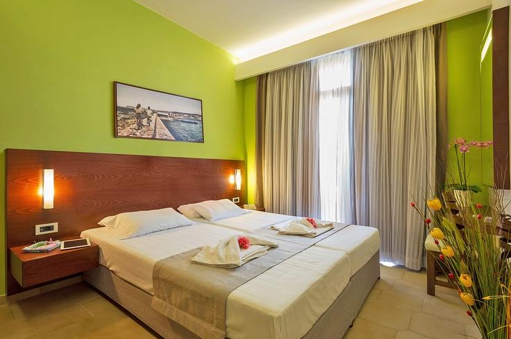 Oscar Suites & Village Studio room interior design. Double bed, night lamps, wall decor, wardrobe, balcony door