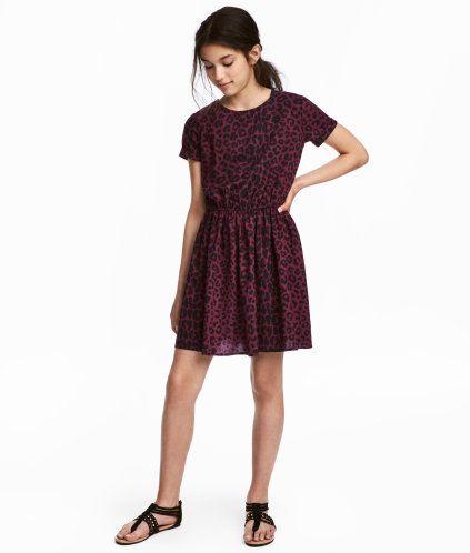 Vinröd/Leopardmönstrad. En kortärmad klänning i vävd viskos. Klänningen har något vidare halsringning med öppning bak och knapp i nacken. Fastsytt uppvik
