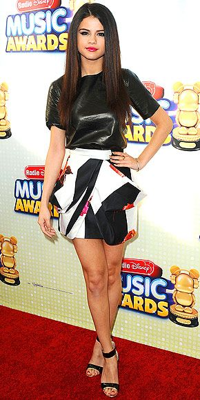 Selena Gomez in leather shirt and Blumarine printed mini skirt to the Radio Disney Music Awards in LA