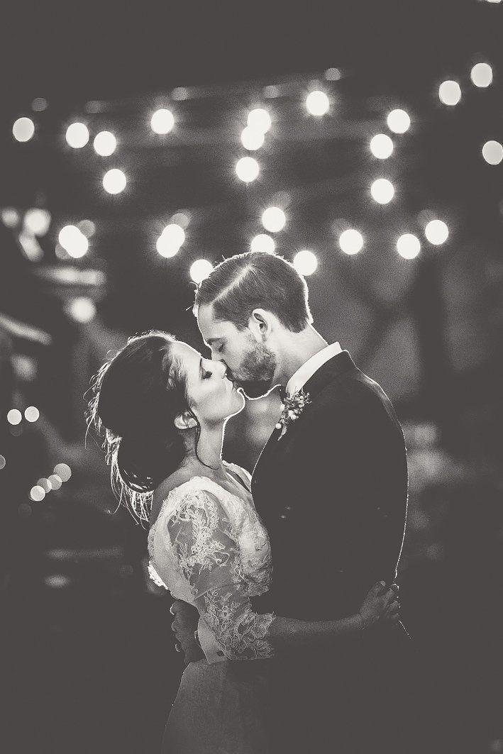 bride and groom photo under festoon lights