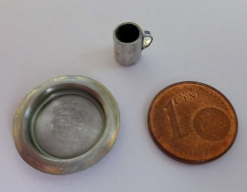 Tin plate and mug. The mug is the shell of a capacitor, Ø6mm and 7mm high, with a metal tape handle. The plate Ø19mm is the back of a mini speaker (so not from a capacitor as those in the link below the picture), cut off to size and sanded.