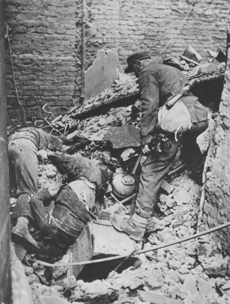Waffen SS NCO checks the bodies of two Polish fighters in the ruins of Warsaw during the Warsaw Uprising, Sept-Oct 1944. German soldiers had strict orders to finish off any Polish fighters discovered still alive. The Germans took very few prisoners.