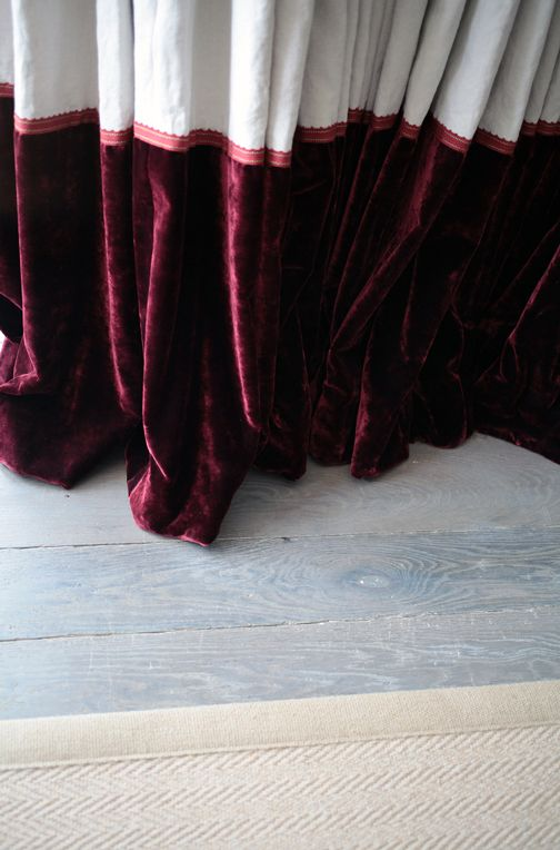SGS Design Ltd.  Natural grey distressed engineered floorboards and sisal rug.  Linen curtains with burgundy velvet contrast border to base and embroidered trim.