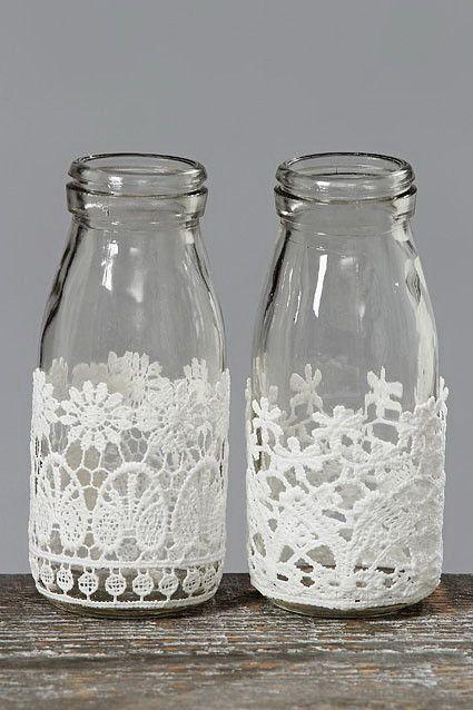 Floreros con botellas de cristal, de esas que nos quedan de los jugos, tés, salsas aderezadas y bebidas de cafés saborizadas. En la parte inferior decore con una aplicación de encaje, o inclusive con blondas de papel.