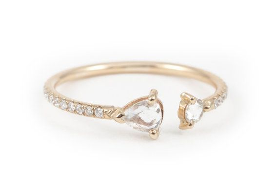 Two rose cut tear shape diamonds (0.25 carats each) are set at each end of the 14 karat gold band.