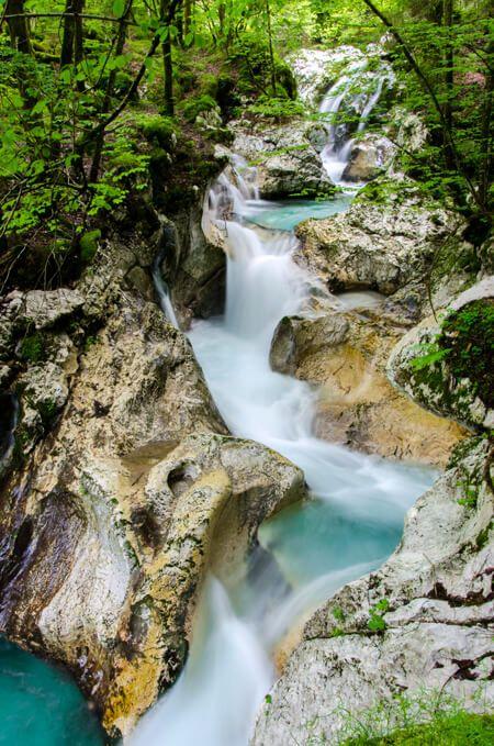 Water paradijsje Lepenjica vlakbij Bovec in Julische Alpen in Slovenië loopt door een kloof met diverse watervalletjes en overal komt water tussen de rotsen vandaan langs de rivier. Er is een grote diversiteit aan planten in dit bosrijke gebied. Je kunt een kleine rondwandeling doen waarbij je een paar keer via een houten brug de Lepenjica oversteekt. / bron www.bovec.si