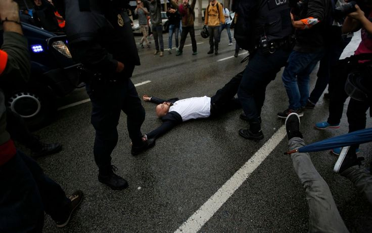 10/1/17 Catalan referendum: Riot police 'fire rubber bullets' at crowd as they block voters at besieged polling stations - latest news  Spanish National Police drags away a man lying on the street as they try to prevent voters from reaching a voting site at a school assigned to be a polling station by the Catalan government in Barcelona