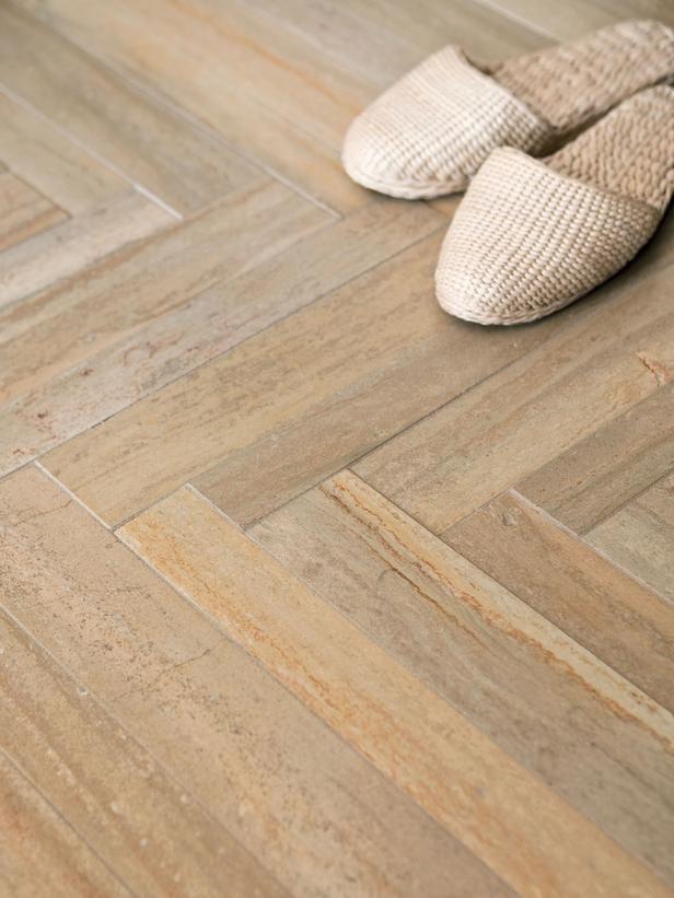 Loving this limestone tile floor for a bathroom: HGTV Remodels; herringbone pattern is gorgeous!
