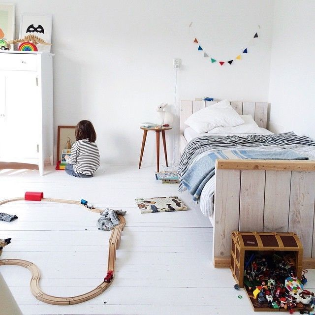 A kids room with a minimal backdrop. We like the bleached wood bed and the wooden floor, but also the splashes of colour with bedding, garlands and toys