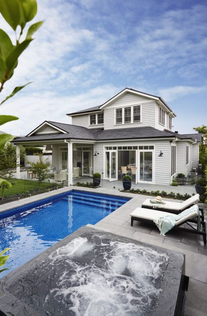 House exterior view of my Hamptons style home featuring shingled roof and grey weatherboards. Gallerie B Interiors