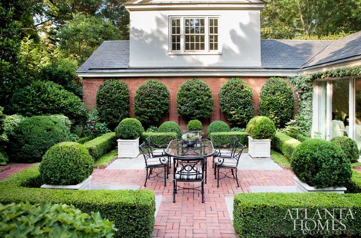 Brick-paved walkways, manicured boxwoods, espaliered shrubs and a dining terrace are only part of the backyard's appeal.