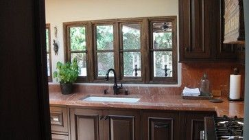 Red marble counter with dark kitchen cabinets. | Spanish Colonial styled Kitchens and Baths mediterranean-kitchen