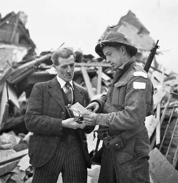 Private Steve W. Buttee of The Highland Light Infantry of Canada talking with M. Albert Collett, who is showing a photograph of his son Paul Collett, Caen, France, 10 July 1944.