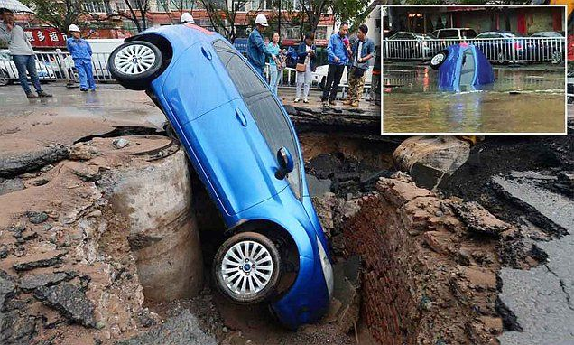 Chinese driver's car is swallowed by massive sinkhole in a flood