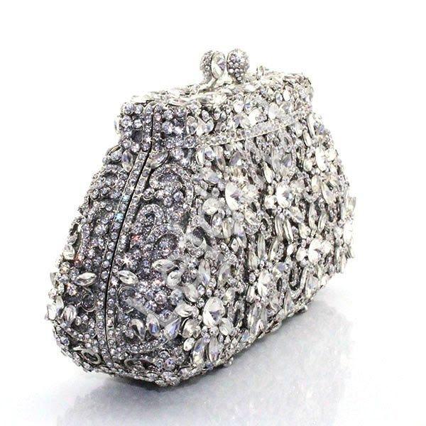 Luksusowa unikalna torebka na wesele, wieczorowa z ażurowymi wzorami  Cudownie błyszcząca torebka, ręcznie zdobiona kryształkami. Ażurowy przepiękny wzór dodaje torebce luksusowego wyglądu. Kryształki ułożone w kwiatowy wzór tworzący niesamowity wzór. Torebka cała zdobiona, posrebrzane okucie i zapięcie wysadzone malutkimi kryształkami. Po otwarciu torebka wyłożona srebrną ekoskórką. Do kompletu dołączone są dwa łańcuszki o gęstym splocie, krótszy i dłuższy. Torebeczka wygląda przepięknie…