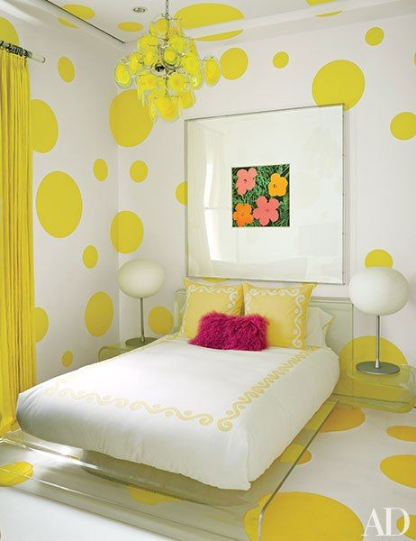 "A Warhol ""Flowers"" work hangs in a guest room that's decked out in a dotted wall treatment devised by Martyn Lawrence Bullard and painted in a Benjamin Moore yellow; the vintage chandelier is by Vistosi, the bedding is by Leontine Linens, and the felt rug is by Anthony Monaco."
